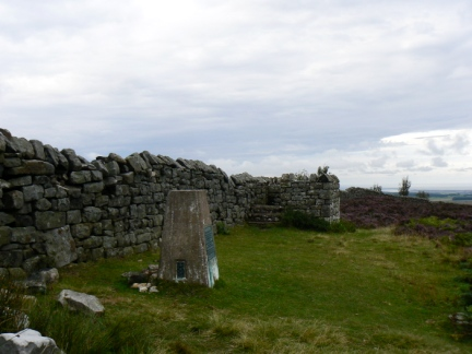 The trig point and viewing platform on the summit of Ros Castle