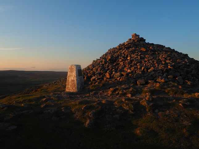 The trig point and large cairn marking the beacon site