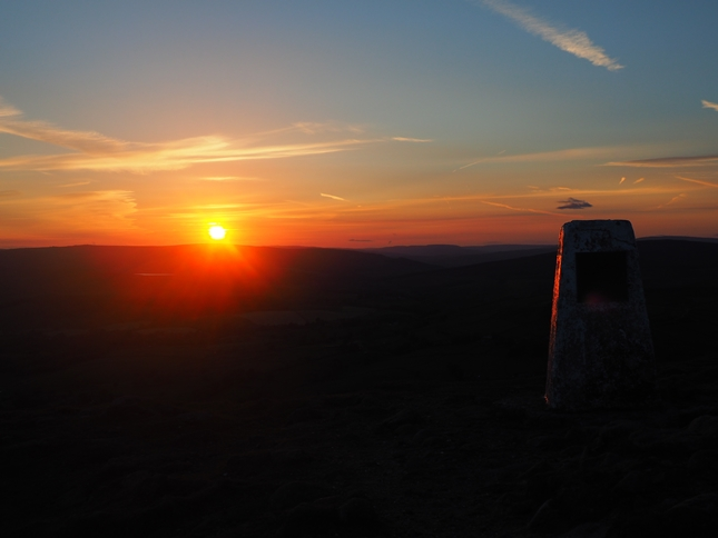 The trig point on Beamsley Beacon as the sun sets