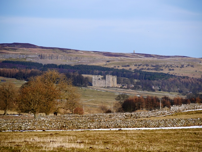 Bolton Castle and the chimney at Cobscar Mill on Redmire Moor