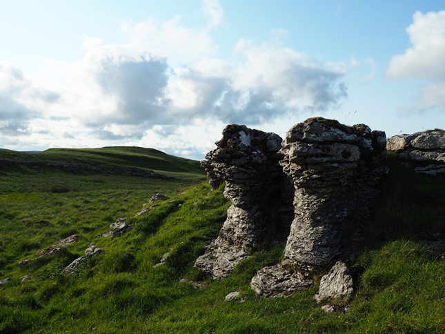 A weathered limestone outcrop with Parson's Pulpit beyond