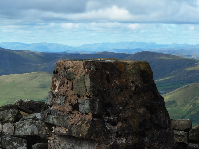 A close up of the trig point on Wild Boar Fell with a long line of Lake District fells in the distance