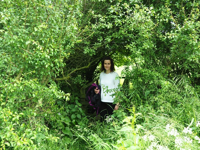 Lisa emerging from a stile in a thick hedge