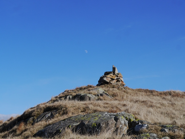 One of the cairns on Long Crag with the moon visible in the sky above
