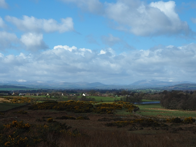 Blencarn and its lake with a backdrop of the Lakeland fells