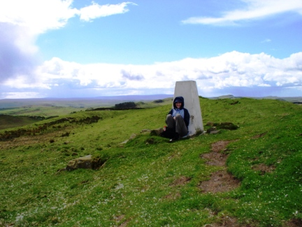 Lisa sat by the trig point on Sewingshields Crag after the hail shower
