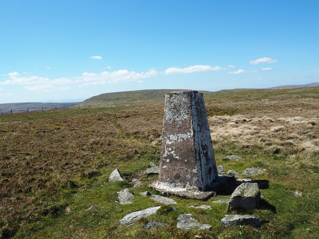 The trig point on Mickle Fell looking back towards the distant summit