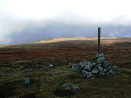 The summit cairn of Backstone Edge looking to Knock Fell