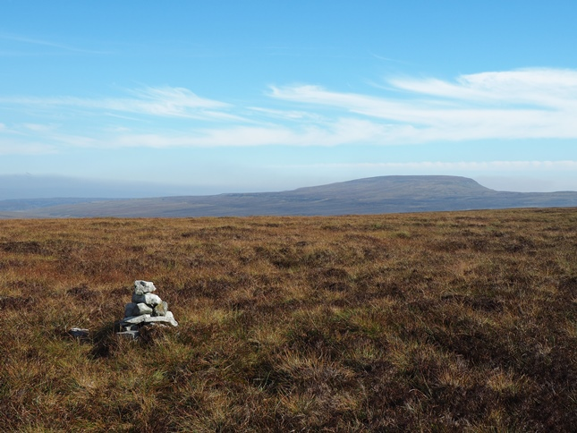 The small pile of stones marking the summit of Murton Fell with Mickle Fell in the distance