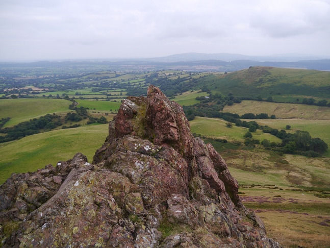 A rocky rib of volcanic rock with the Clee Hills in the far distance