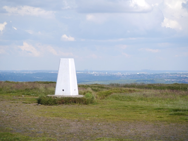The trig point on Baildon Hill with Leeds in the distance