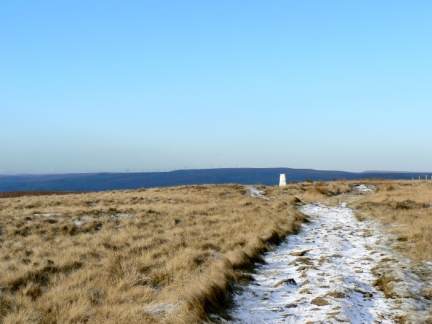 The trig point on White Hill with the Scout Moor Windfarm in the distance