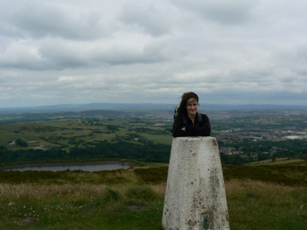 Lisa by the trig point with the Bowland fells in the distance