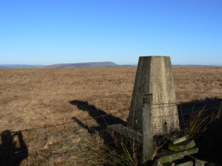 The trig point on Hameldon Hill with Pendle Hill in the distance